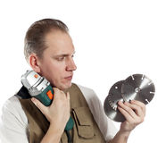 Half-length portrait of the builder in green working overalls and a white t-shirt with the construction tool in hands Royalty Free Stock Image