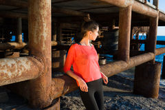 Half length portrait of charming female runner taking break after workout while standing near pier construction on the beach Royalty Free Stock Images