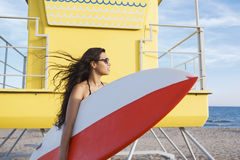 Half length portrait of a charming Latin women holding surfing board with copy space for your brand Royalty Free Stock Photography