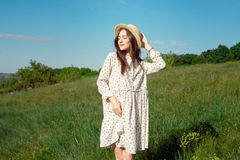 Half length portrait of a charming positive woman dressed in long white summer dresses with a straw hat of happy smiles stock photography