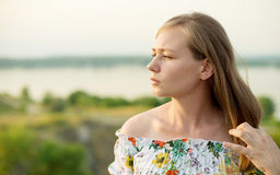 Half length portrait of charming positive woman is looking epically off into the distance in sunset background Stock Images