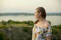 Half length portrait of charming positive woman is looking epically off into the distance in sunset background Royalty Free Stock Images