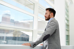 Half length portrait of a confident businessman conceived looks in office window while rest after conference Royalty Free Stock Photography