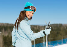 Half-length portrait of female alps skier with skis in hands Stock Photo