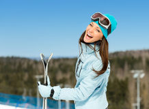 Half-length portrait of female downhill skier with skis in hands Royalty Free Stock Images
