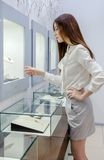 Half-length portrait of girl looking at jewelry in showcase Stock Photo