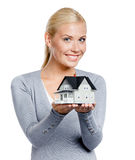 Half-length portrait of girl with model house. Half-length portrait of girl in grey pullover with small model house, isolated on white Royalty Free Stock Photo