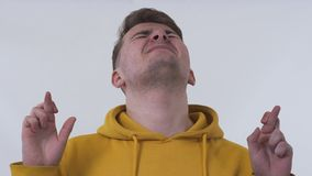 Half-length portrait of a man wearing yellow sweatshirt standing crossing his fingers with closed eyes wanted to make. Half-length portrait of handsome man stock video