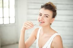Half-length portrait of happy beautiful dark-haired woman wearing in white singlet with spoon in mouth Stock Photo