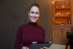 Half length portrait of a happy businesswoman holding touch pad while sitting in cozy restaurant interior, Stock Images