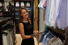 Half length portrait of happy female entrepreneur using digital tablet for job in her modern store with men's clothes Stock Photo