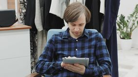 Half length portrait of happy male entrepreneur using digital tablet for job in her modern store with woman`s clothes stock footage