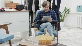 Half length portrait of happy male entrepreneur using digital tablet for job in her modern store with woman`s clothes stock video footage