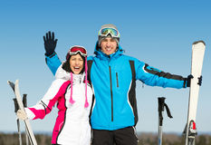 Half-length portrait of hugging skiers. Half-length portrait of two hugging skiers with skis in hands royalty free stock image