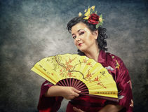 Half-length portrait of kimono mature woman with fan Royalty Free Stock Photo