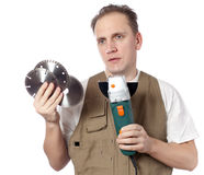 Half-length portrait of the man of the builder in green working overalls and a white t-shirt with the construction tool in hands o Stock Photo