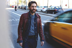 Half length portrait of a smiling handsome bearded man dressed in cool clothes walk in urban setting in autumn day Stock Image