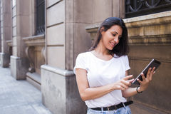 Half length portrait of a smiling latin woman looking photo on her digital tablet computer while walking on the street Royalty Free Stock Photography