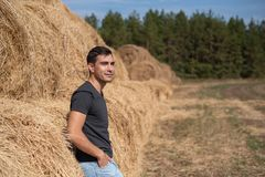 Half-length portrait of a smiling man farmer in a gray t-shirt stands with his back to the hay looks in the field, haymaking, harv. Half-length portrait of stock photos