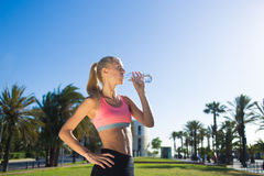 Half length portrait of tired athletic woman dressed in sport wear refreshing with energy drink after jog Royalty Free Stock Photos