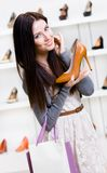 Half-length portrait of woman handing heeled shoe Royalty Free Stock Image