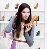 Half-length portrait of woman handing high heeled shoe Stock Photos