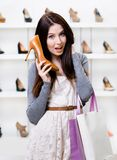 Half-length portrait of woman handing shoe Stock Photos