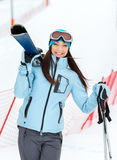 Half-length portrait of woman handing skis Royalty Free Stock Photo