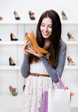 Half-length portrait of woman keeping heeled shoe Royalty Free Stock Images