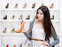 Half-length portrait of woman keeping shoe Stock Photography