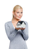 Half-length portrait of woman with model house. Half-length portrait of woman in grey pullover with small model house, isolated on white Royalty Free Stock Images