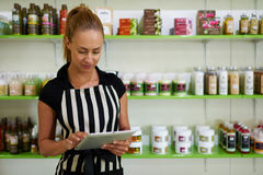Half length portrait of woman owner reading something on touch pad while standing against shelves with cosmetic products Stock Image
