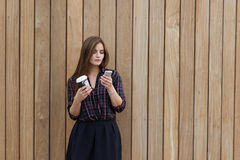 Half length portrait of a woman reading text message on her mobile phone while standing with take away coffee outdoors, Stock Photo