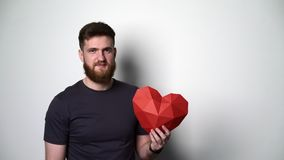 Half length portrait of young bearded hipster man holding red heart shape stock video footage