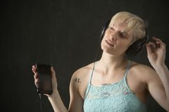 Young blonde woman in blue camisole dancing with headphones on. Half length portrait of young blonde woman in blue camisole with headphones on and holding a royalty free stock photography