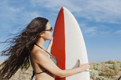 Half length portrait of a young brunette hair model in bikini preparing for surfing in the ocean in sunny day Stock Images