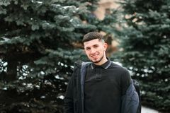 Half length portrait of young brutal guy with beard in black winter jacket stock photos