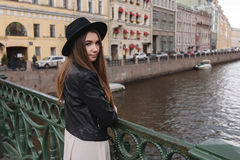 Half length portrait of young charming woman dressed in trendy clothes posing while standing on a river bridge Stock Photos