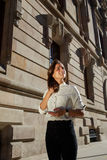 Half length portrait of young dreaming female strolling in urban setting in spring sunny day, attractive woman using mobile phone Royalty Free Stock Photos