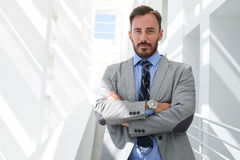 Half length portrait of a young handsome businessman with crossed arms standing in white hallway of his company Stock Photos