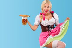 Young sexy Oktoberfest girl - waitress, wearing a traditional Bavarian dress, serving big beer mugs on blue background Stock Photo