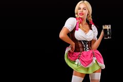 Closeup portrait of Oktober fest girl - waitress, wearing a traditional Bavarian dress, serving big beer mugs on black. Half-length portrait of young blonde with royalty free stock photography