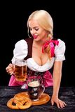 Closeup portrait of Oktober fest girl - waitress, wearing a traditional Bavarian dress, serving big beer mugs on black. Half-length portrait of young blonde with stock images