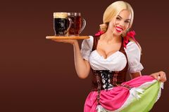 Closeup portrait of Oktoberfest girl - waitress, wearing a traditional Bavarian dress, serving big beer mugs on brown Stock Photo