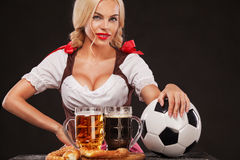 Young sexy Oktoberfest girl - waitress, wearing a traditional Bavarian dress, serving big beer mugs and taking soccer Royalty Free Stock Photo