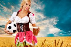 Young sexy Oktoberfest girl - waitress in Munich, wearing a traditional Bavarian dress, serving big beer mugs on golden Stock Photography