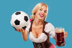 Young sexy Oktoberfest girl - waitress, wearing a traditional Bavarian dress, serving big beer mugs and taking soccer Stock Images