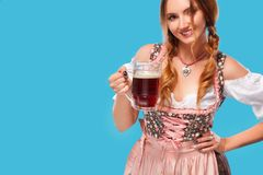 Young sexy Oktoberfest girl - waitress, wearing a traditional Bavarian dress, serving big beer mugs on blue background. Royalty Free Stock Photos