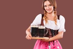 Young sexy Oktoberfest girl - waitress, wearing a traditional Bavarian dress, serving big beer mugs on brown background. Stock Images