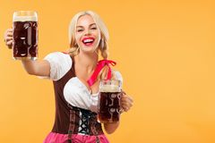 Young sexy Oktoberfest girl - waitress, wearing a traditional Bavarian dress, serving big beer mugs on orange background Royalty Free Stock Image